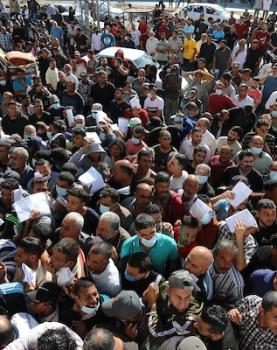 مواطنون فلسطينيون ينتظرون أمام مقر الغرفة التجارية للتسجيل من اجل العمل في إسرائيل، في دير البلح وسط قطاع غزة