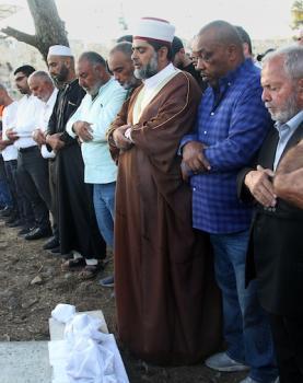 فلسطينيون يؤدون الصلاة على بقايا الرفات من القبور التي هدمتها قوات الاحتلال الإسرائيلي في المقبرة اليوسفية في القدس، قبل إعادة دفنها مرة أخرى